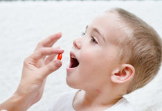 Child receiving pill - closeup Royalty Free Stock Photography