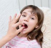 Child receiving pill - closeup Royalty Free Stock Photos