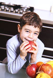 Child with red apple. In the kitchen Royalty Free Stock Photos