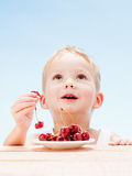 Child with red berries, boy eats and chooses cherry. Blue sky background stock photos