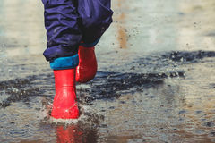 Child with red boots is jumping into a puddle. Child with red boots is jumping into a puddle in raining spring or autumn outdoor. Toning instagram filter Royalty Free Stock Photos