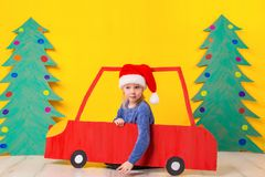 Child in red Christmas car. Xmas holiday concept. Child in red Christmas car. A painted car and green Christmas tree made of cardboard on a yellow background Stock Image