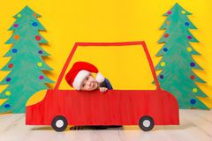 Child in red Christmas car. Xmas holiday concept. Child in red Christmas car. A painted car and green Christmas tree made of cardboard on a yellow background Stock Photography