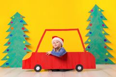 Child in red Christmas car. Xmas holiday concept. Child in red Christmas car. A painted car and green Christmas tree made of cardboard on a yellow background Royalty Free Stock Images