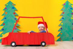 Child in red Christmas car. Xmas holiday concept. Child in red Christmas car. A painted car and green Christmas tree made of cardboard on a yellow background Stock Images