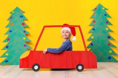 Child in red Christmas car. Xmas holiday concept. Child in red Christmas car. A painted car and green Christmas tree made of cardboard on a yellow background Royalty Free Stock Photography