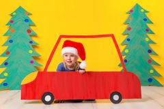Child in red Christmas car. Xmas holiday concept. Child in red Christmas car. A painted car and green Christmas tree made of cardboard on a yellow background Stock Photos