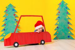 Child in red Christmas car. Xmas holiday concept. Child in red Christmas car. A painted car and green Christmas tree made of cardboard on a yellow background Stock Photo