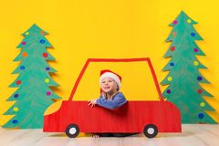 Child in red Christmas car. Xmas holiday concept. Child in red Christmas car. A painted car and green Christmas tree made of cardboard on a yellow background Royalty Free Stock Image