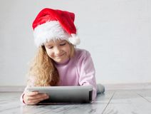Child in red christmas hat with tablet Stock Photos