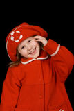 The child in a red coat. And a red cap smiles, having taken a hand in a head Stock Photo