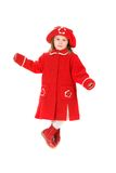 Child in a red coat. The child in a red coat and a red cap smiles Stock Image