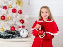 Child red costume hold christmas ornament ball. Christmas ball traditional decor. Kids can brighten up christmas tree by royalty free stock images