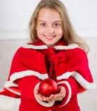 Child red costume hold christmas ornament ball. Kids can brighten up christmas tree by creating their own ornaments stock image