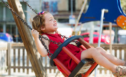 Child in red dres on chain swing Royalty Free Stock Photography