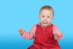 Child with red dress. Portrait of a girl with red dress and pacifier royalty free stock photography