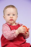 Child with red dress. Portrait of a girl with red dress and  a tomato in the hands royalty free stock images