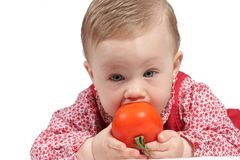 Child with red dress. Portrait of a girl with red dress and tomato royalty free stock images