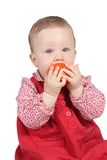 Child with red dress. Portrait of a girl with red dress and a tomato in the hands stock photo