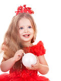Child  in red dress holding christmas ball. Stock Photo