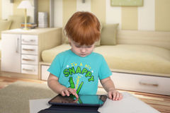 The child with red hair  plays with pad Stock Photo