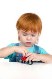The child with red hair  plays with toy Royalty Free Stock Images