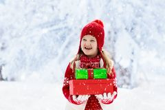 Child in red hat with Christmas presents and gifts in snow. Winter outdoor fun. Kids play in snowy park on Xmas eve. Little girl. In knitted sweater, scarf and stock photos