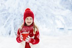 Child in red hat drinking hot chocolate in snow on Christmas vacation. Winter outdoor fun. Kids play in snowy park on Xmas eve. Little girl in knitted sweater royalty free stock photography