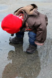 Child with red hat playing in the puddle of water Stock Photography