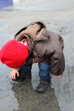 Child with red hat playing in the puddle of water Stock Photos