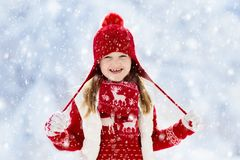 Child playing in snow on Christmas. Kids in winter stock photography