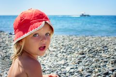 The child in a red hat sits on the seashore. The child in a red hat sits on the beach by the sea Royalty Free Stock Image