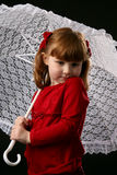 Child in red holding white lace parasol. Cute girl in red dress holding a white lace parasol Stock Photos