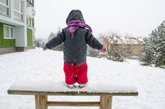 Child with red pants standing wooden bench snow Royalty Free Stock Image