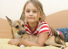 Child with a red puppy. Lays on a bed of yellow color Royalty Free Stock Image