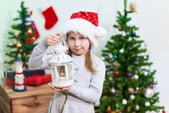 Child in a red Santa hat standing near Christmas tree with lantern with burning candle inside. Child in a red Santa hat standing near Christmas tree with a Stock Photo