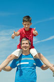 Child in a red shirt sitting on his father Stock Photo