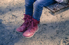 Child with red shoes in swing Royalty Free Stock Photos