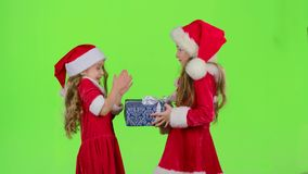 Child gives a New Year gift to her friend. Green screen. Child in a red suit gives a New Year`s gift a surprise to her friend. Green screen stock footage