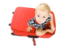 Child on red suitcase. Cute child  sitting on the big red suitcase Royalty Free Stock Photography