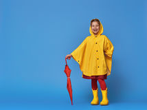 Child with red umbrella. Happy funny child with red umbrella posing on blue wall background. Girl is wearing yellow raincoat and rubber boots Stock Photo