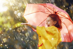Child with red umbrella. Happy funny child with red umbrella under the autumn shower. Girl is wearing yellow raincoat and enjoying rainfall. Kid playing on the royalty free stock photography