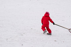 Child with red waterproof overall outdoor winter Stock Images