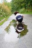Child reflection. A child playing in the rain water in the forest with her reflection in that water Stock Photography