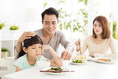 Child refuses to eat while family dinner Stock Image