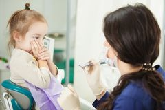 Child refuses to go through medical procedure in dentist office. And female doctor in facial mask and rubber gloves holds modern electric appliance for teeth Royalty Free Stock Image