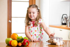 Child refusing harmful food in favor of vegetables. Child girl refusing harmful food in favor of vegetables Stock Images