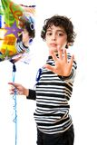 Child Refusing to be photographed during his birthday party. Holding a balloon and serious expression in his face Royalty Free Stock Photo