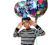 Child Refusing to be photographed during his birthday party.over white background and with balloons Stock Photos