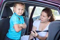 Child refusing to seat into infant car safety seat Royalty Free Stock Image